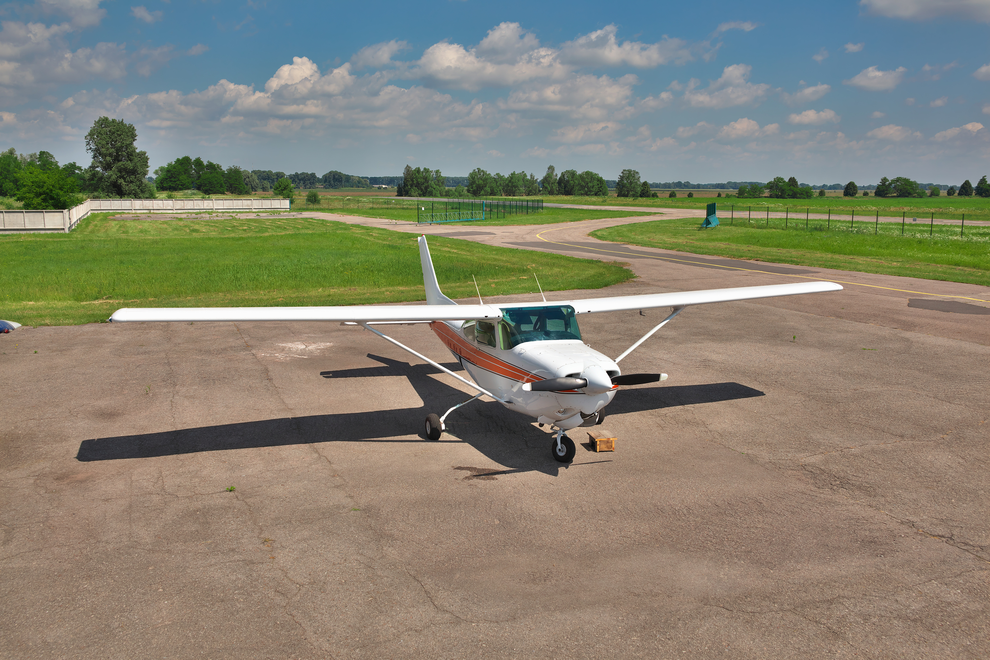 Light Private Plane Parked on the Apron of an Airfield in Summer